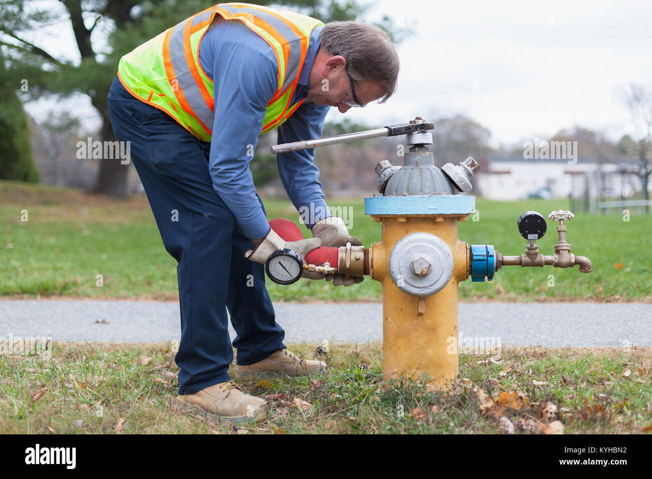 Technician installing hydrant attachment with sensor for flushing mains - Stock Image
