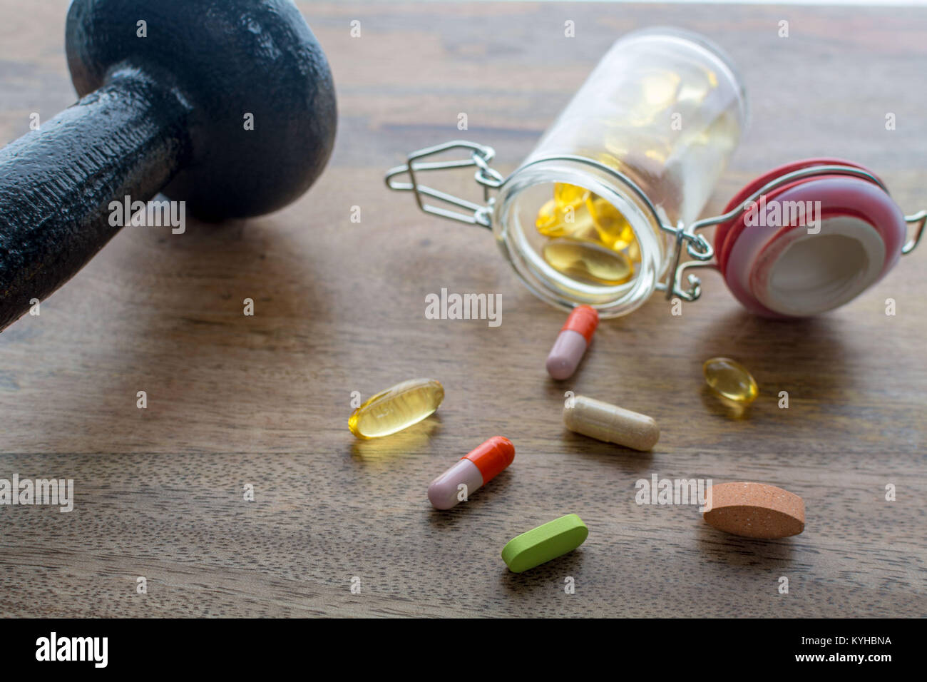 Closeup on dumbbell and dietary supplements on wooden table: fitness and weight loss concept. - Stock Image