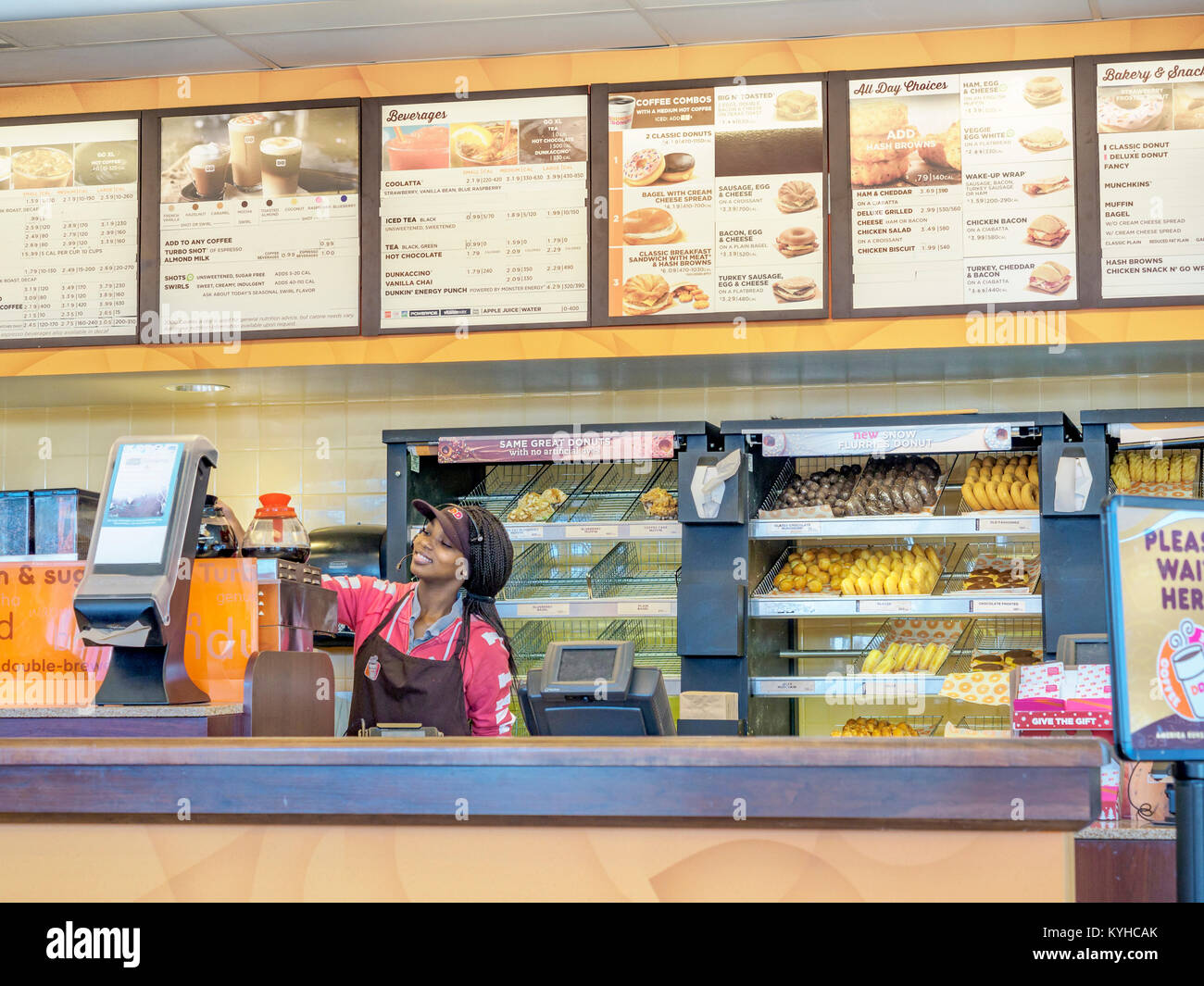 Female African-American fast food worker at the counter of Dunkin Donuts in Montgomery, Alabama United States. - Stock Image