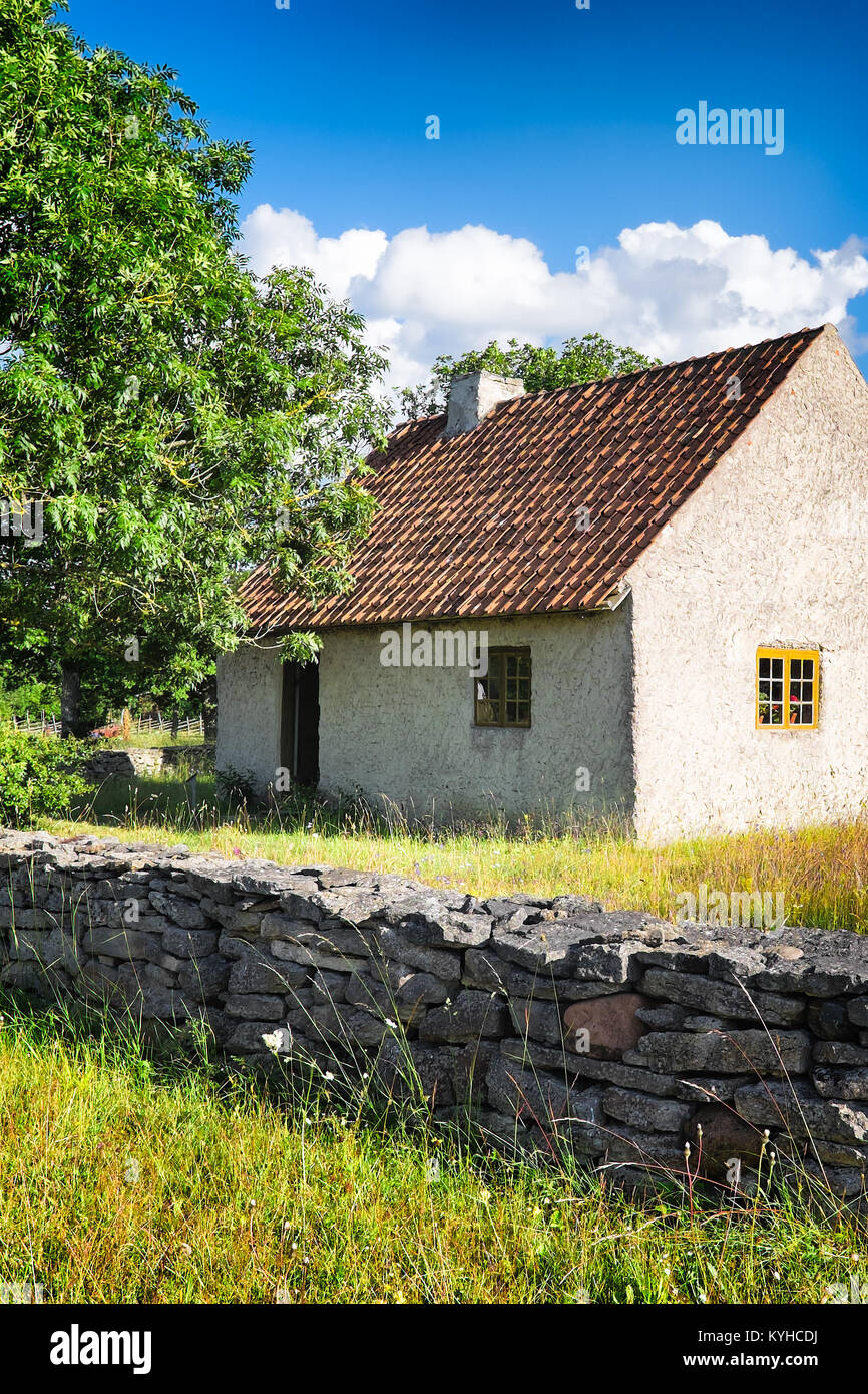 Swedish farm house with an old stone wall. Location: Gotland Island countryside. - Stock Image