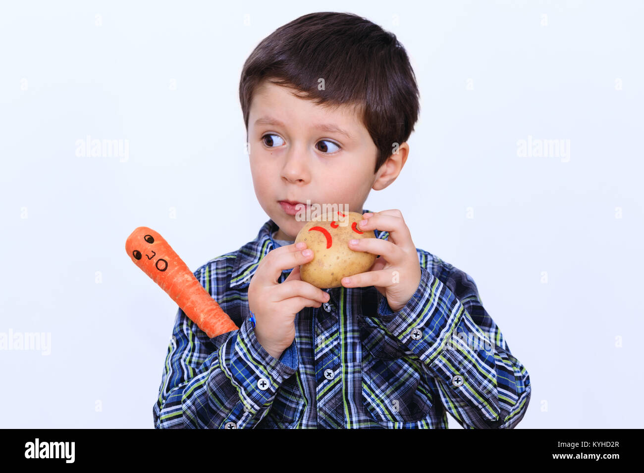 Cute boy intrigued by the feelings of vegetables - Stock Image