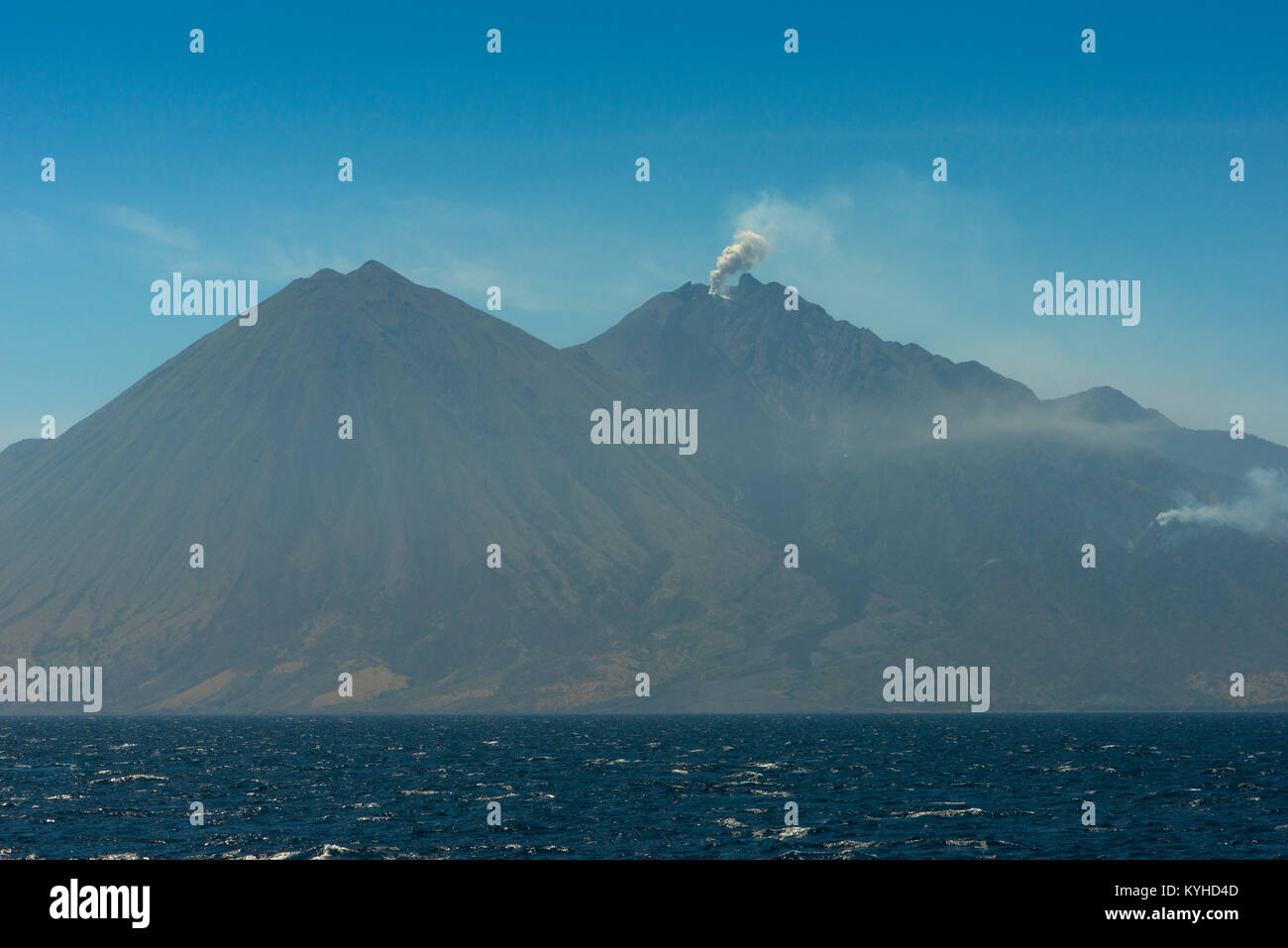 A view of the volcano peaks and a small eruption of the active volcano Sangeang Api (Gunung Api) off the northeast - Stock Image