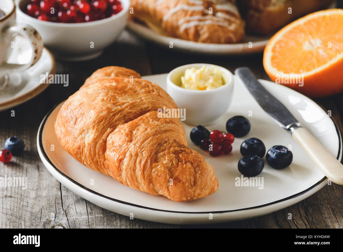 Croissant with fresh berries and butter. Coffee, berries and fruits on background. Concept of continental breakfast. - Stock Image