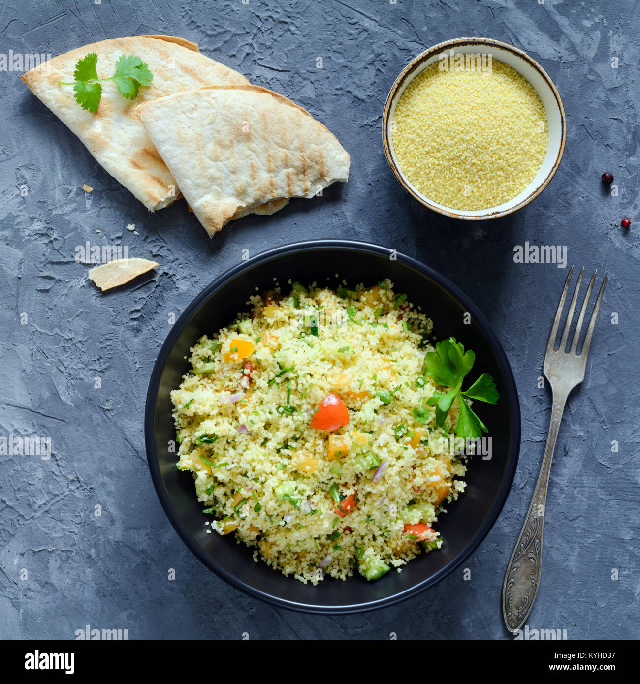 Tabbouleh salad and flatbread on concrete background. Lebanese, arabic cuisine. Healthy vegan cous cous salad in - Stock Image