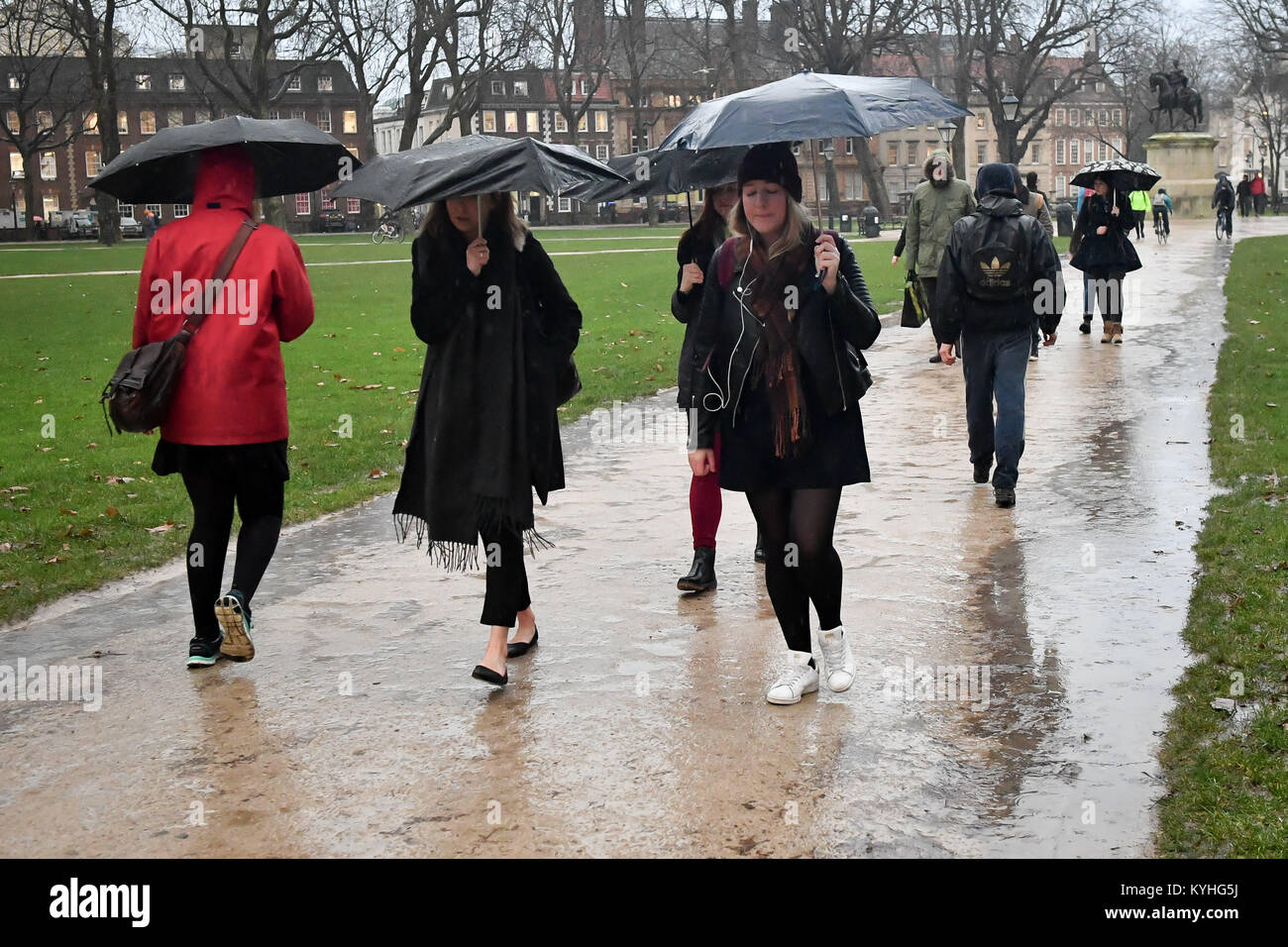 People shelter under umbrellas in pouring rain as they commute to work in Bristol city centre, on what is claimed - Stock Image