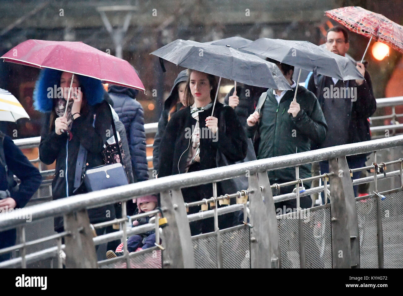 People shelter under umbrellas in pouring rain as they commute to work over Millennium Bridge, Bristol, on what - Stock Image
