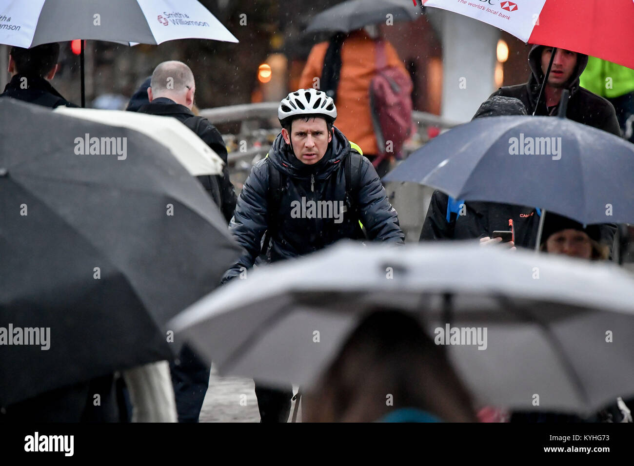 A cyclist passes people sheltering under umbrellas in pouring rain as they commute to work over Millennium Bridge, - Stock Image