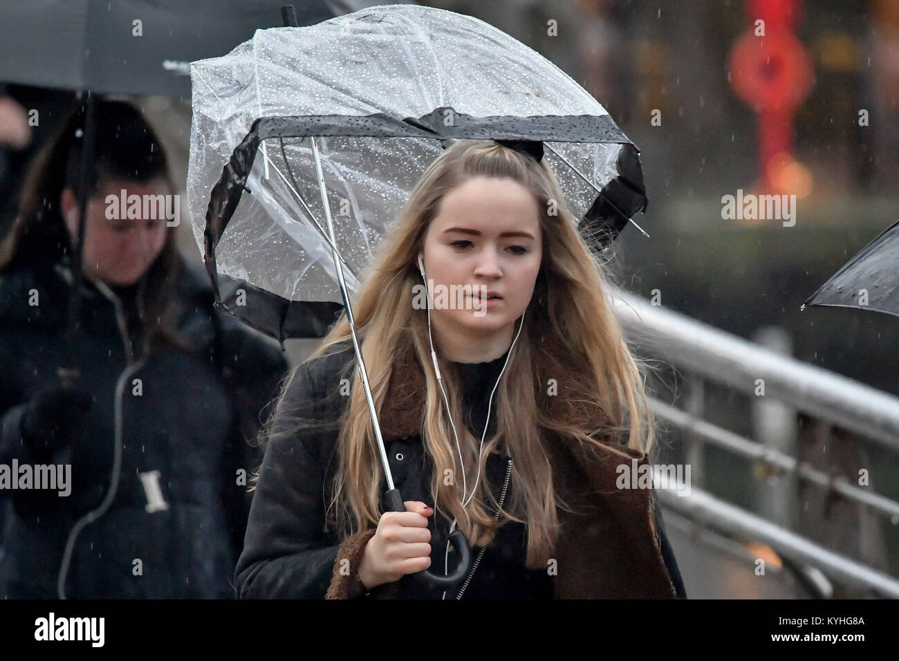 A woman shelters under an umbrella in pouring rain as people commute to work over Millennium Bridge, Bristol, on - Stock Image