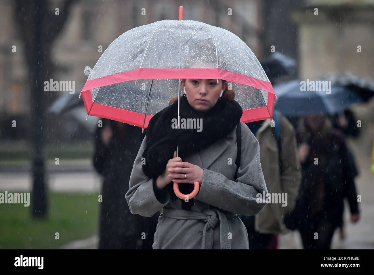 A woman holds an umbrella in pouring rain as people commute to work through Queen's Square in Bristol, on what - Stock Image