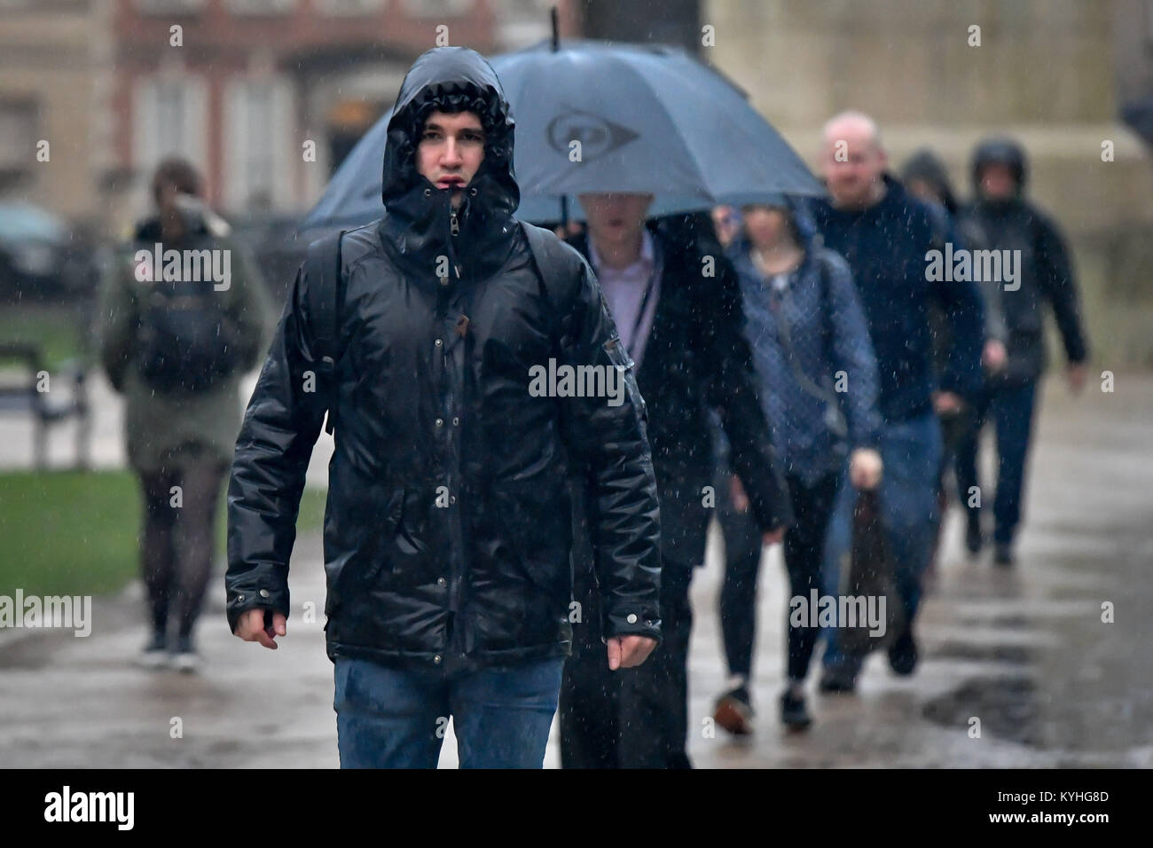 A man walks in pouring rain as people commute to work through Queen's Square in Bristol, on what is claimed - Stock Image