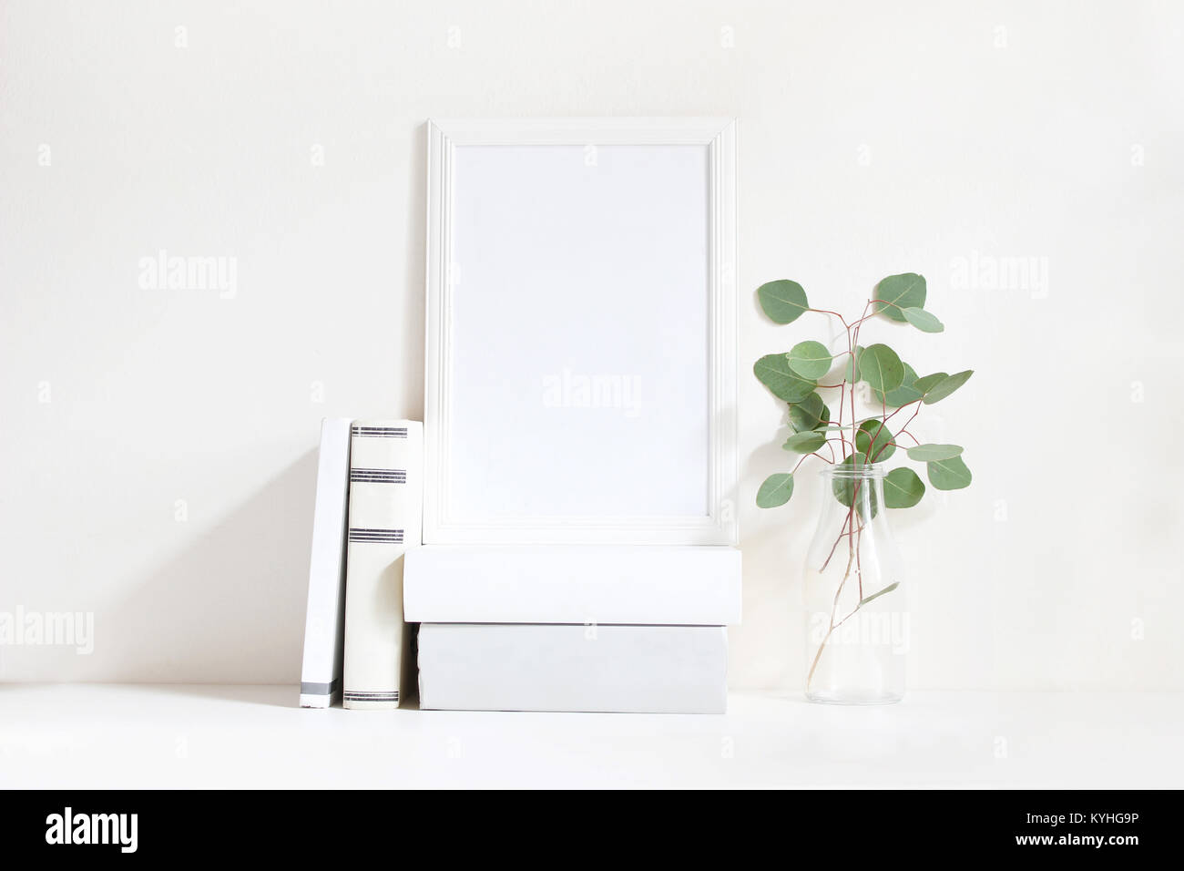 White blank wooden frame mockup with a green eucalyptus branches in glass bottle and pile of books lying on the - Stock Image