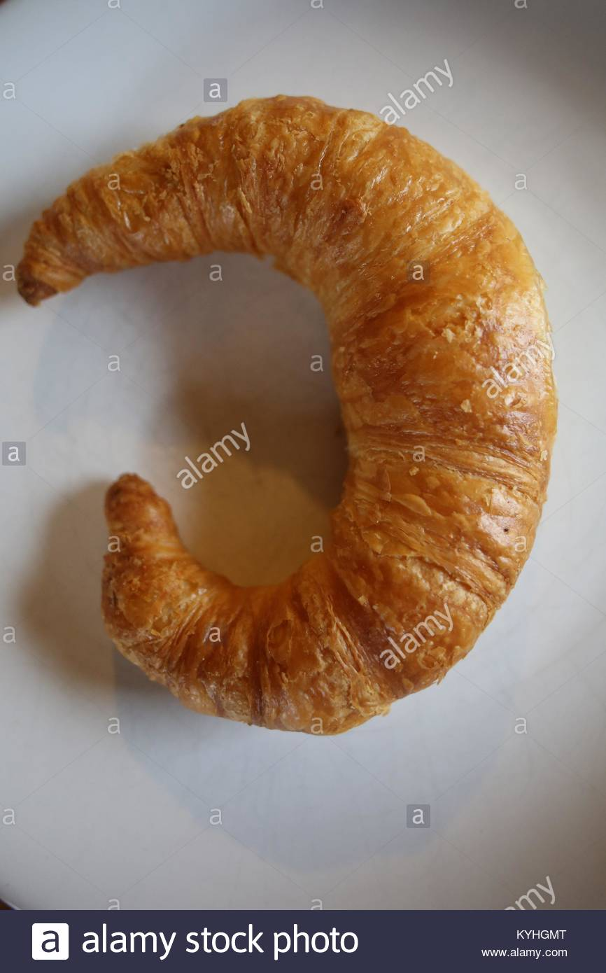 A Bamberg butter croissant on a white plate at breakfast  time. - Stock Image
