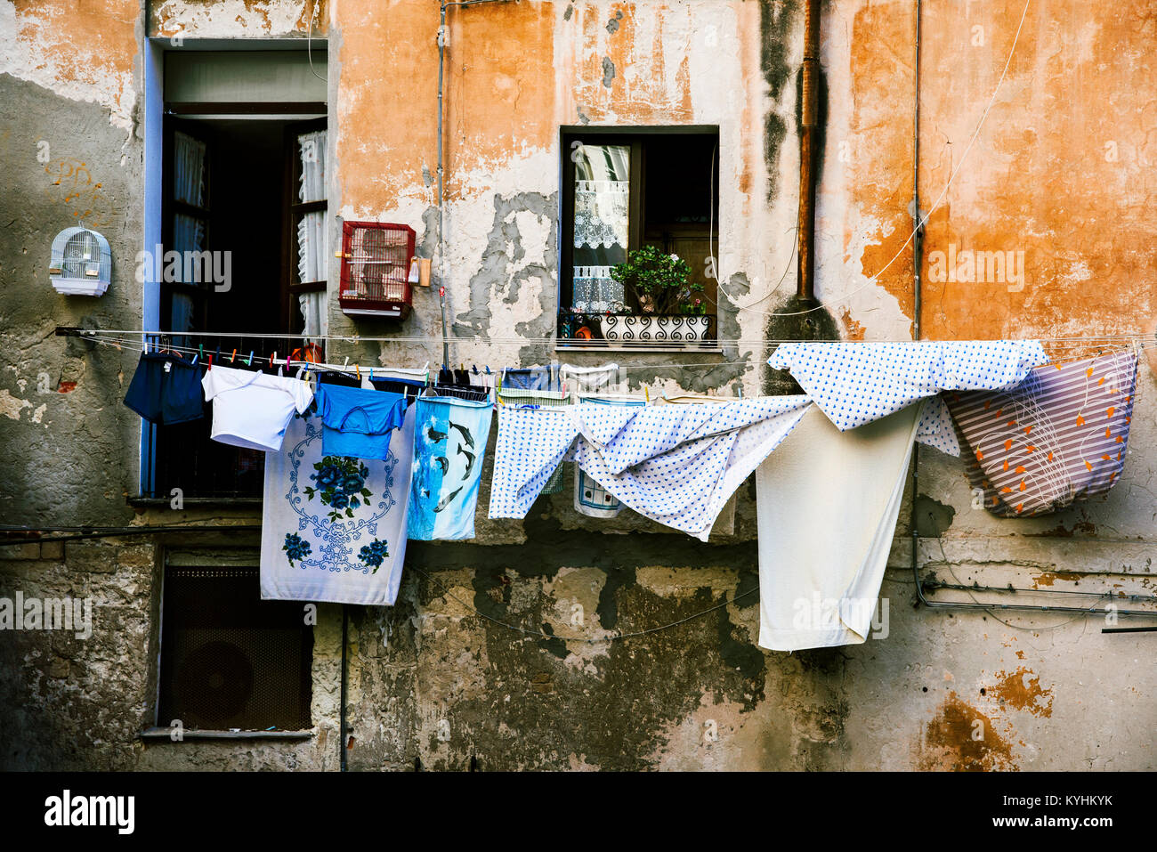 clothes hanging in some clothes lines outdoors in an old building, in the old town of Cagliari, in Sardinia, Italy - Stock Image