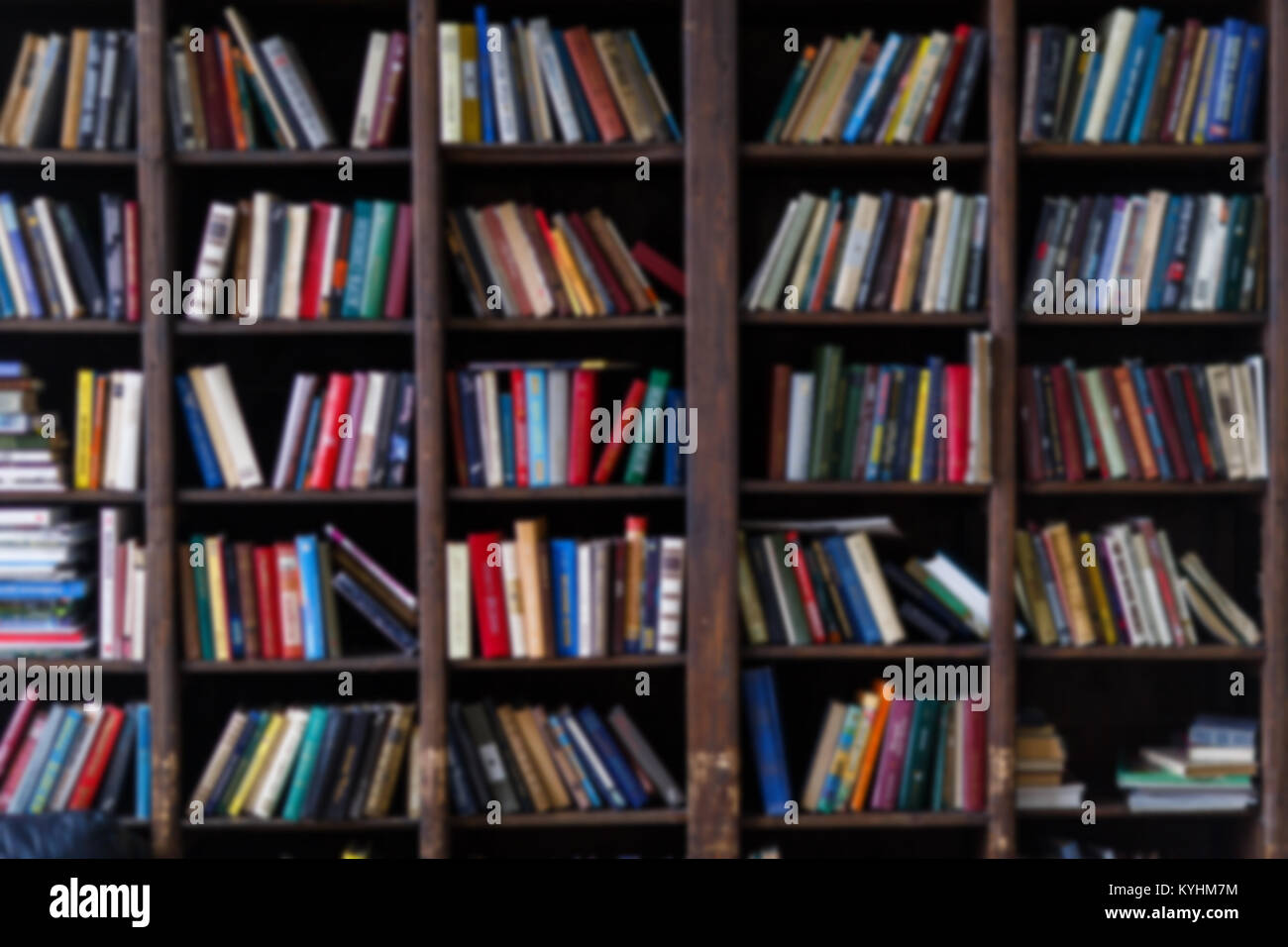 Blurred photo of colorful books in shelves - Stock Image