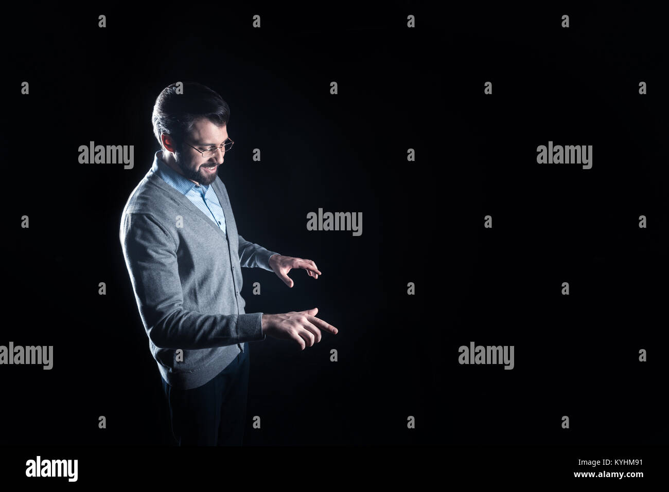 Positive smart man looking at the transparent device - Stock Image