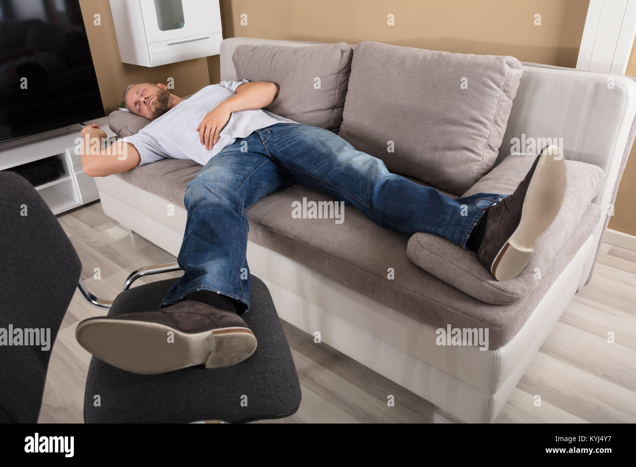 Young Man Sleeping On Couch In Living Room Stock Photo