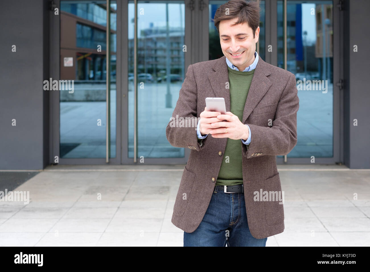 Man texting a message on his smartphone - Stock Image