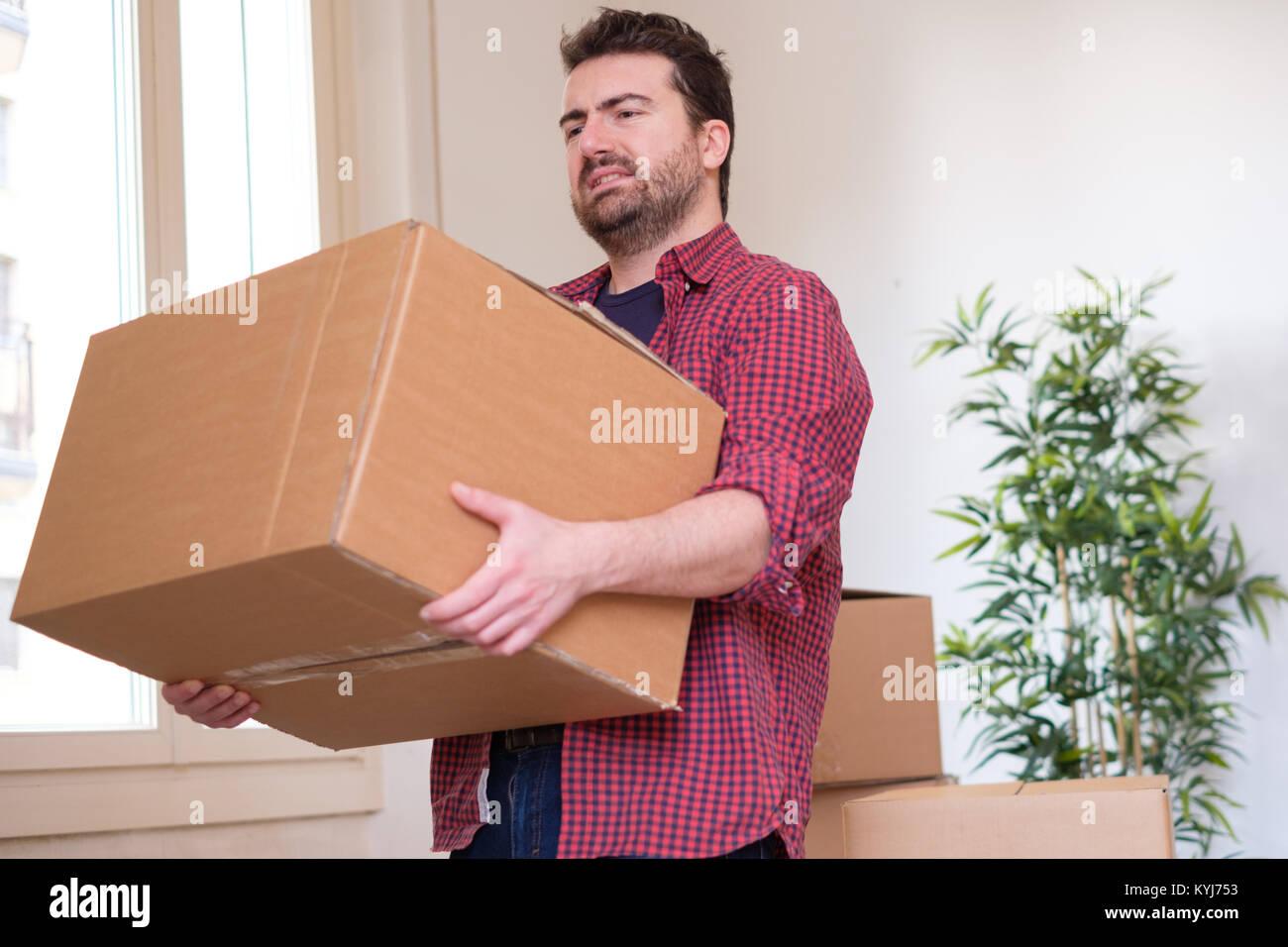 Man feeling back ache cramp moving heavy boxes - Stock Image