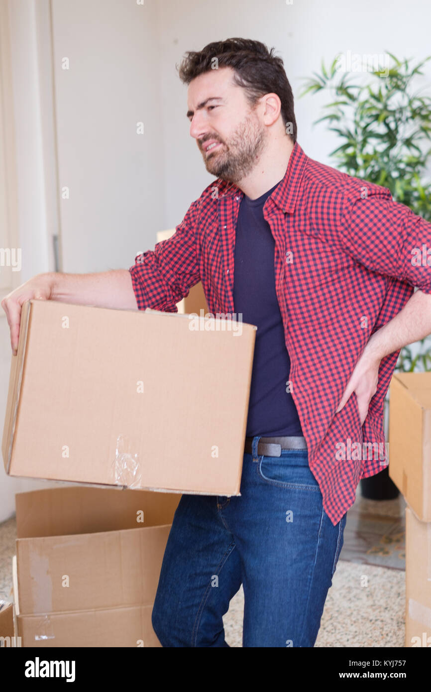 Man moving boxes and feeling back pain because heavy weight - Stock Image