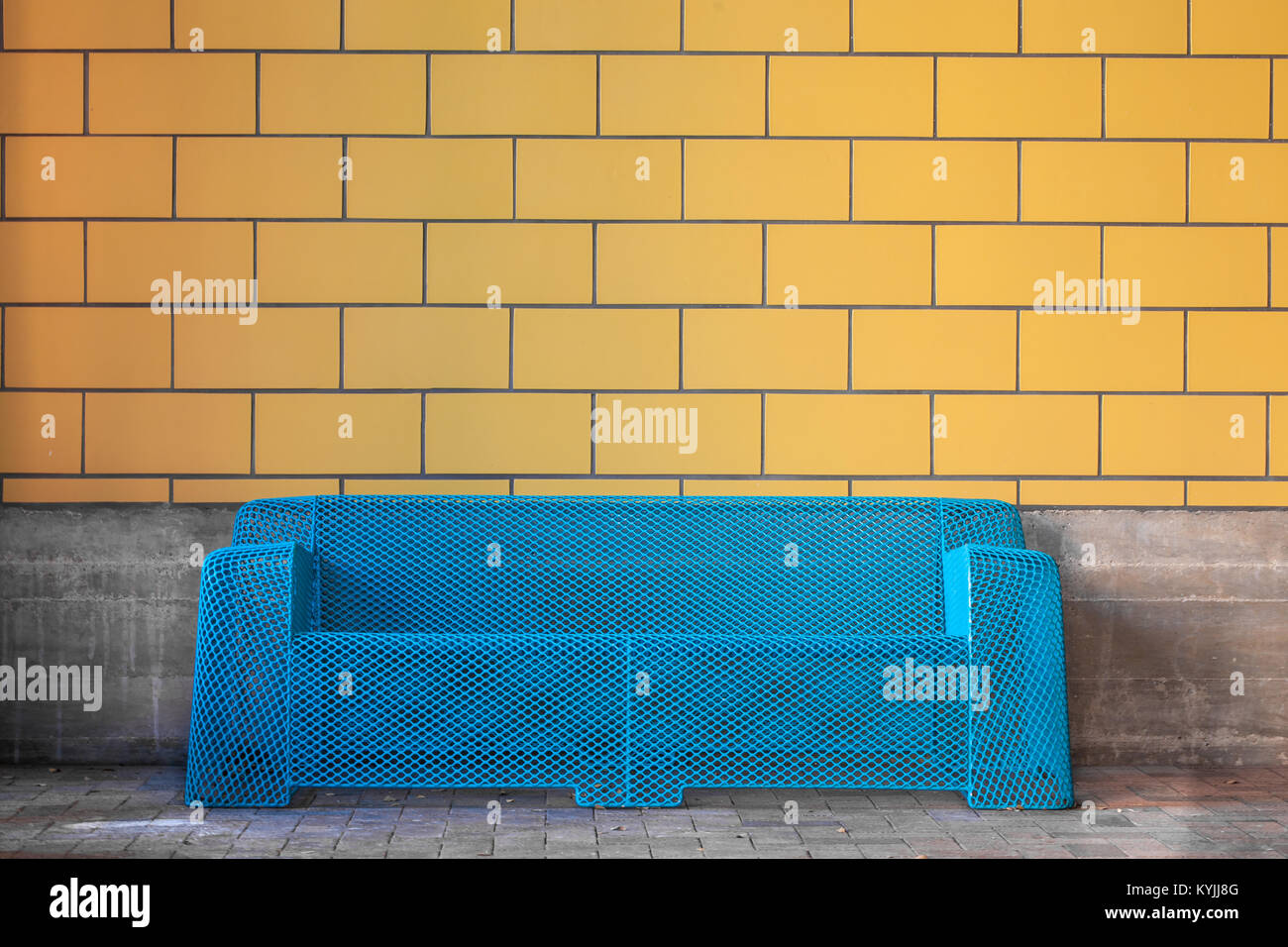 Modern blue metal sofa against yellow tile wall/ Urban furniture Stock Photo