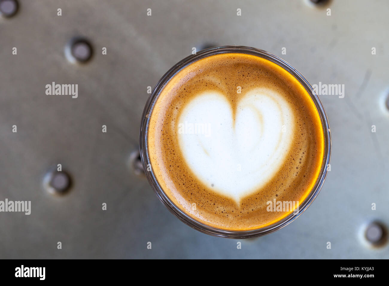 Top view of cortado coffee in a glass with the foam in shape of heart - Stock Image