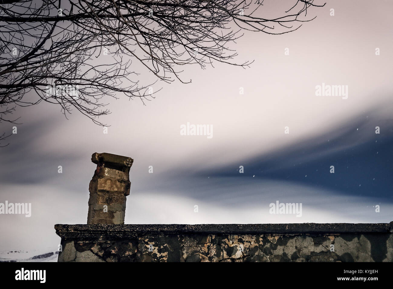 Night starry sky under a veil of white smoky clouds over the roof of an old abandoned house, beautiful nature near Stock Photo