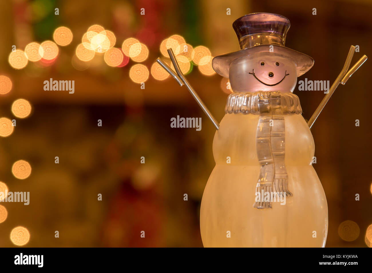 Winter Time Crystal Holiday Snowman in front of a fireplace mantle decorated for the holidays. Stock Photo
