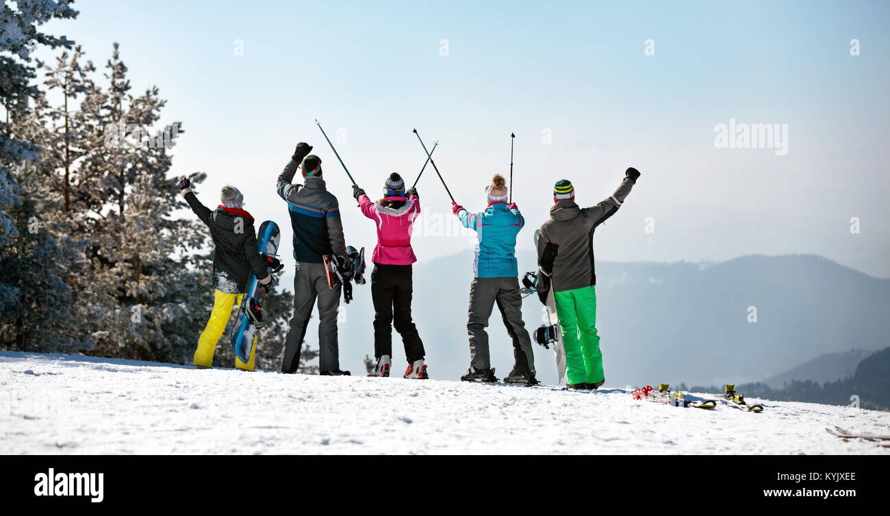 Back view of happy skiing group on the mountain top on sunny day. - Stock Image