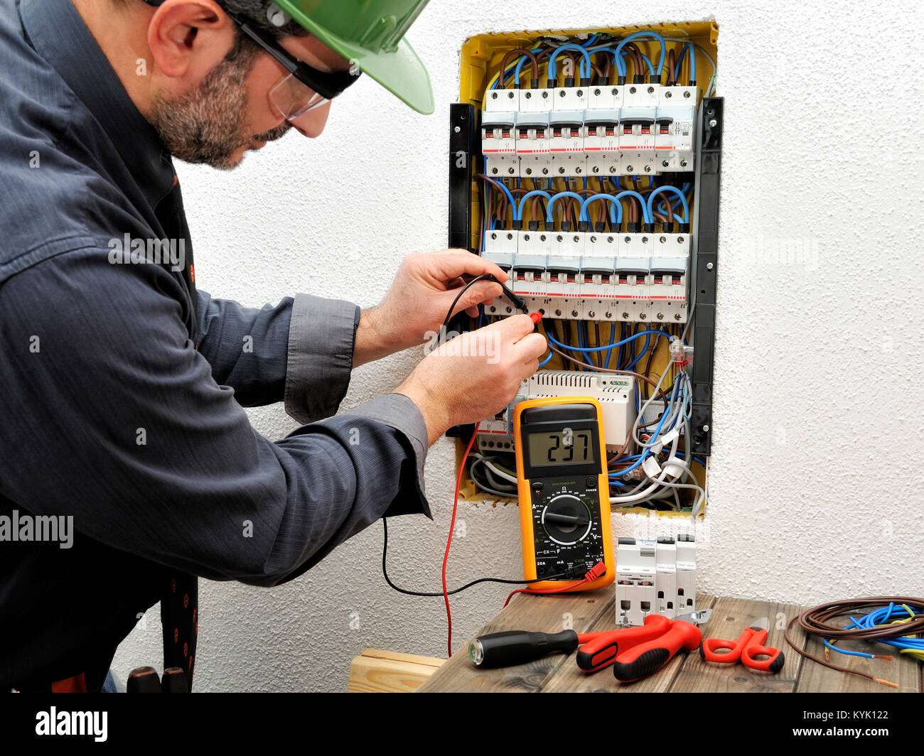 Technical electrician measures the voltage of a circuit breaker of a residential electrical panel - Stock Image