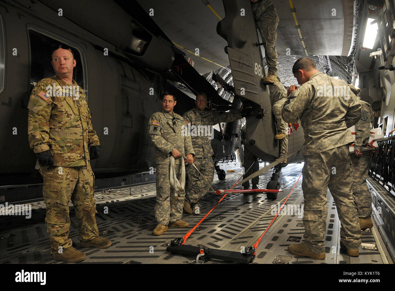 Soldiers with the 63rd Theater Aviation Brigade and Airmen with Hawaii's 204th Airlift Squadron load two UH - Stock Image