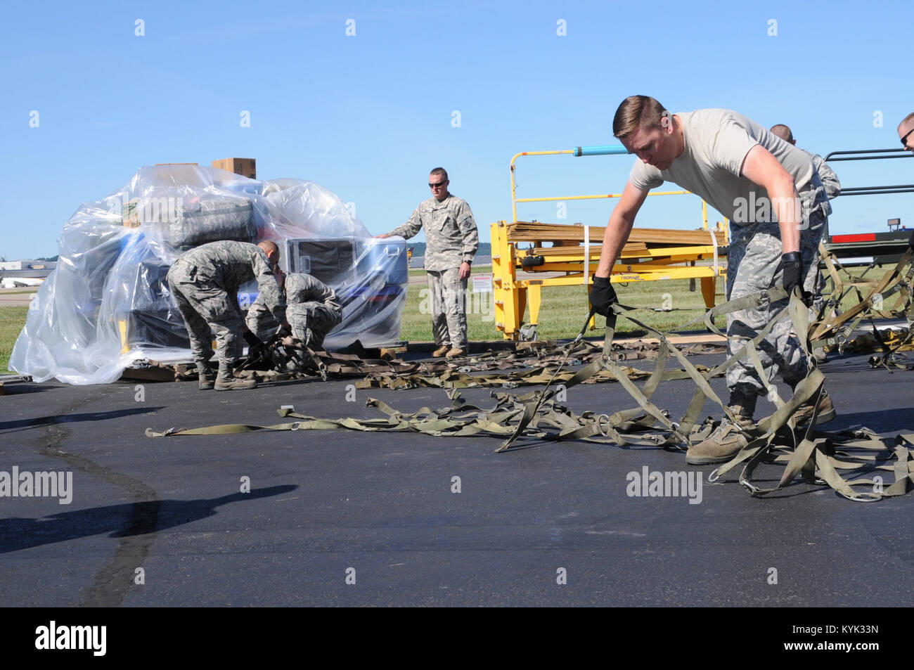 Airmen with the 204th Airlift Squadron, Hawaii National Guard, ready the tie down staps prior to the loading of - Stock Image