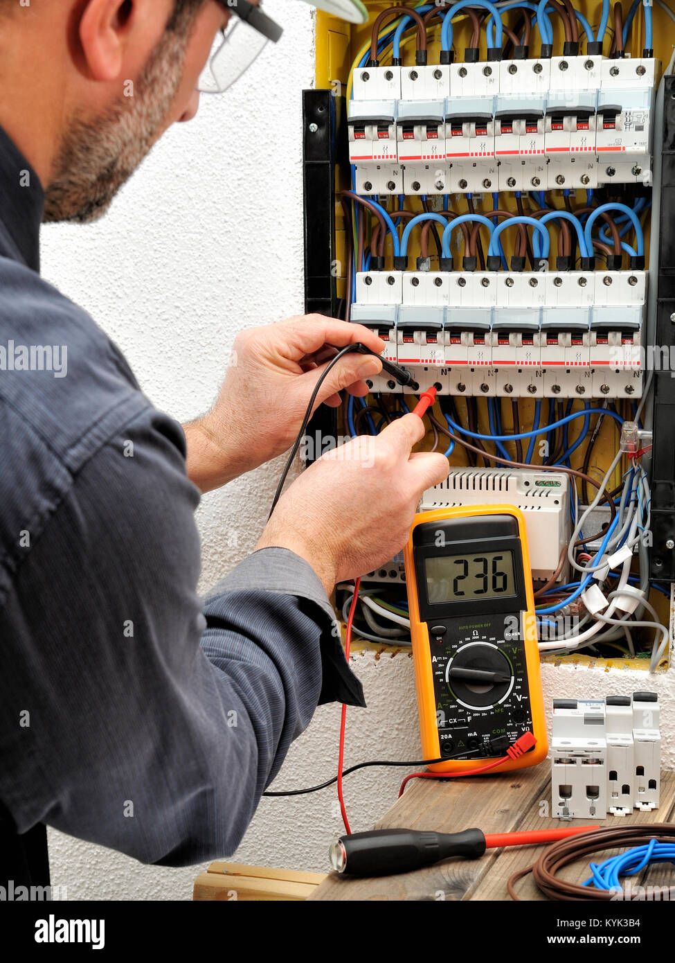 Technical electrician measures the voltage of a circuit breaker of a ...