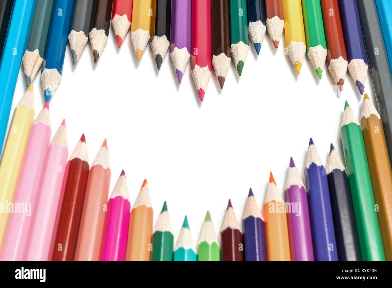 Set of colored pencils lined in heart shape, isolated on white background - Stock Image