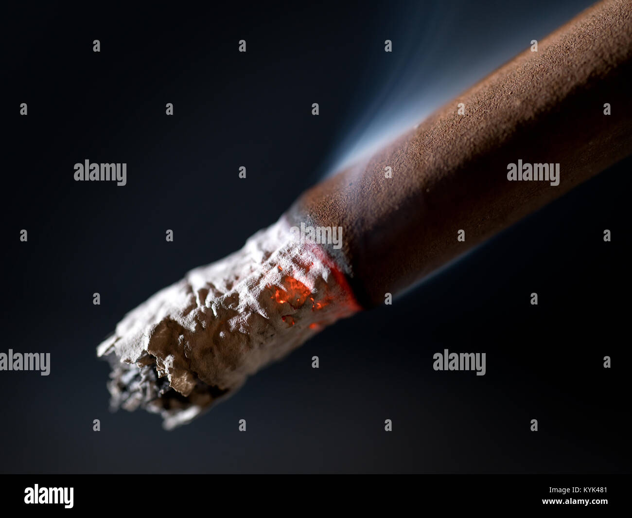 Burning brown cigar with smoke extremal close up. On abstract black background - Stock Image