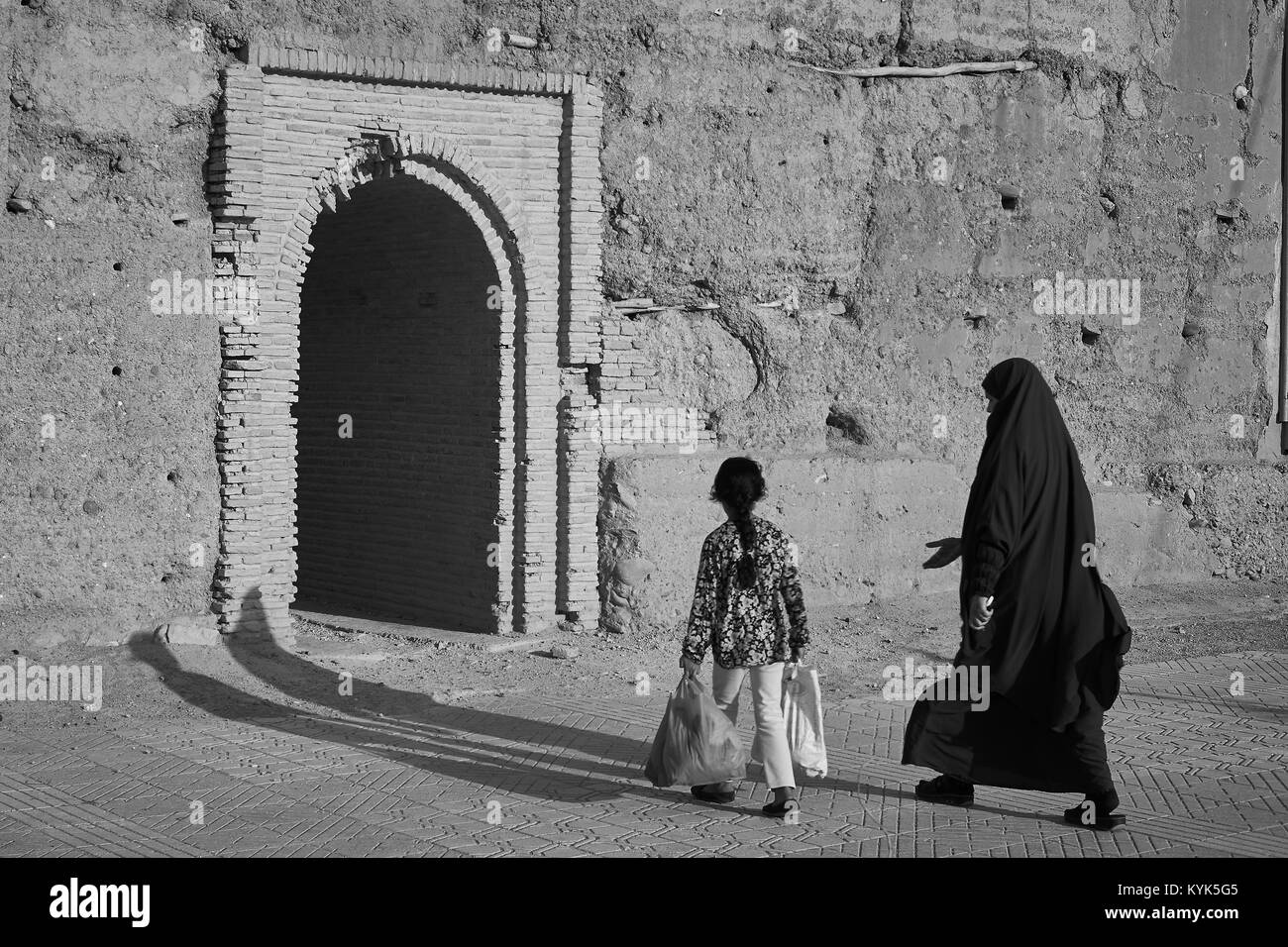 Morrocan veiled woman and little girl walking to fortification door taroudant morocco stock