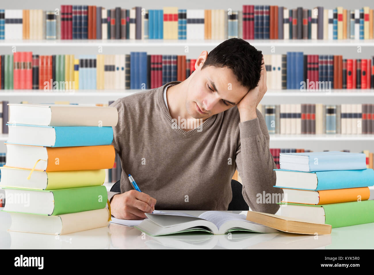 Stressful University Student Studying In Front Of Bookshelf At Library - Stock Image
