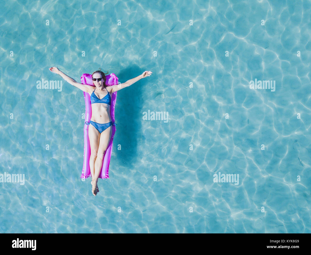 happy woman tourist on vacation, summer holidays on the beach, girl in bikini floating on the mattress in turquoise - Stock Image