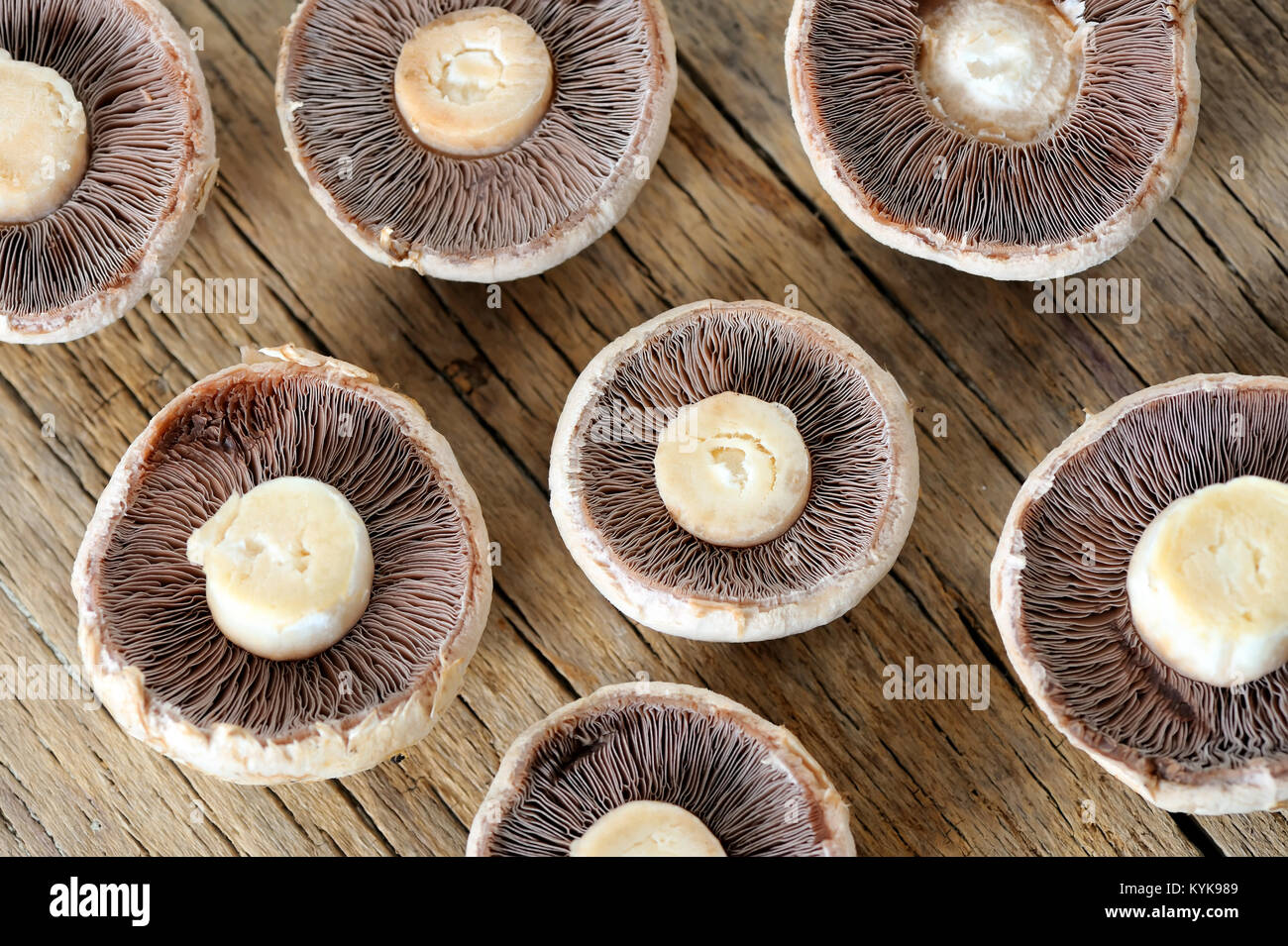 Sliced mushrooms on old wooden table - Stock Image