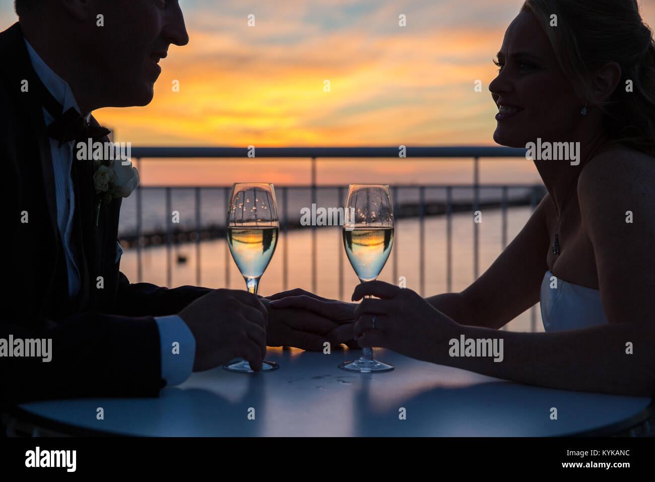 Wine glasses on balcony overlooking St Kilda pier at sunset - Stock Image