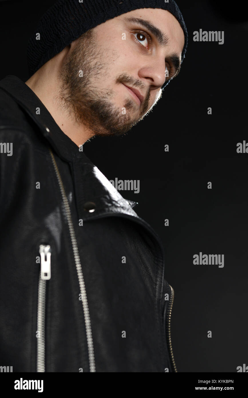 Rock singer portrait, with leather jacket and a cool attitude on black background, studio shot - Stock Image