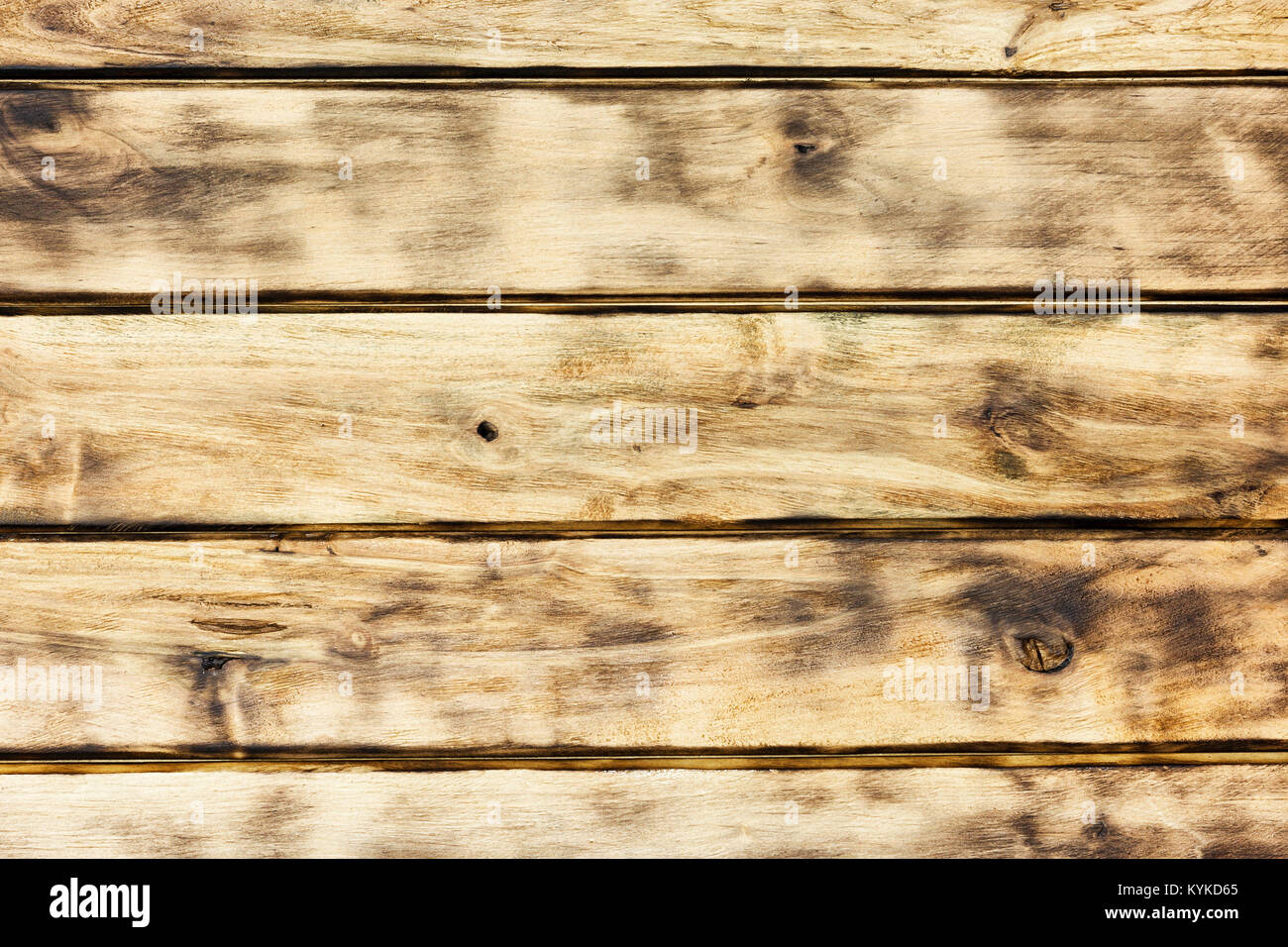 The wooden surface of the horizontal boards with black annealed places Stock Photo