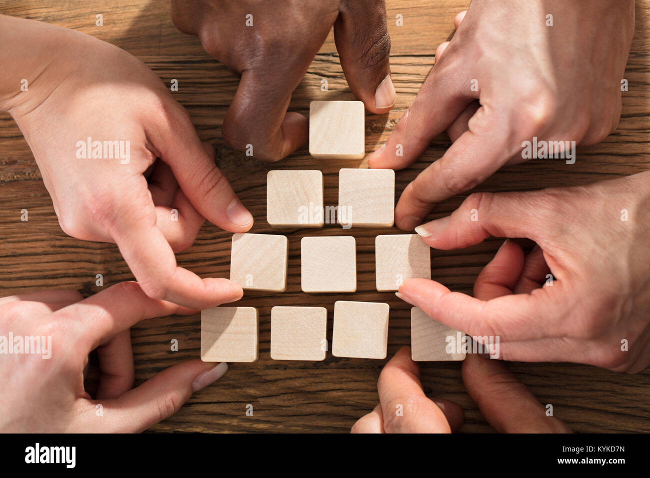 Close-up Of A People Arranging Block On Pyramid Over The Wooden Table Stock Photo