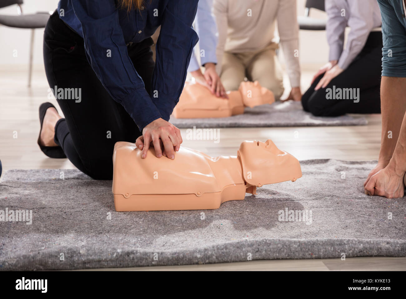 Young Students Practicing CPR Chest Compression On Dummy - Stock Image