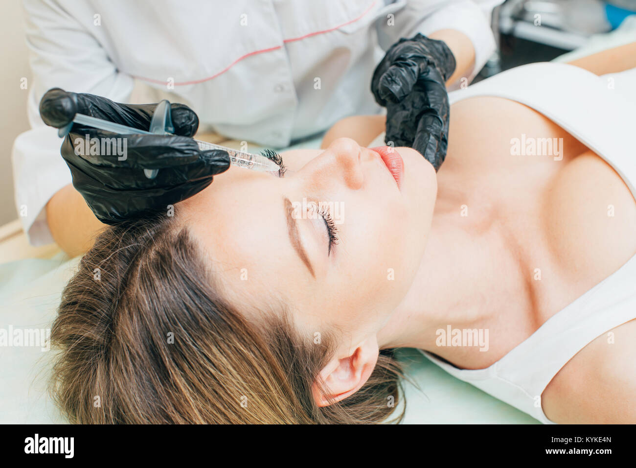 Plastic Surgery. Closeup Of Beautician Hands Holding Syringe Near Female Facial Skin Doing Injections.  Cosmetology. - Stock Image