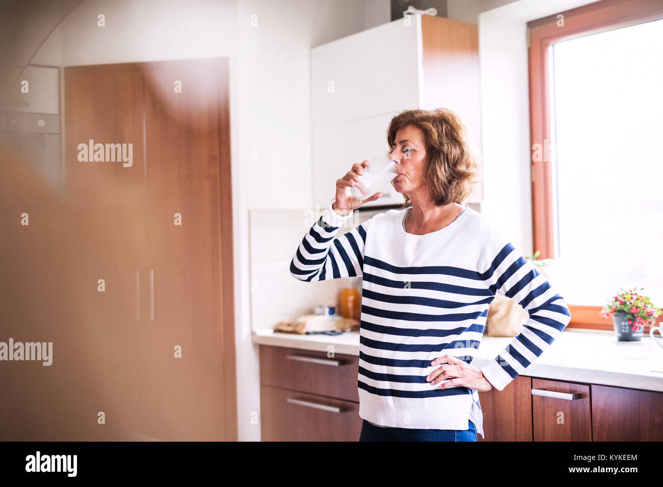 Senior woman drinking water in the kitchen. - Stock Image