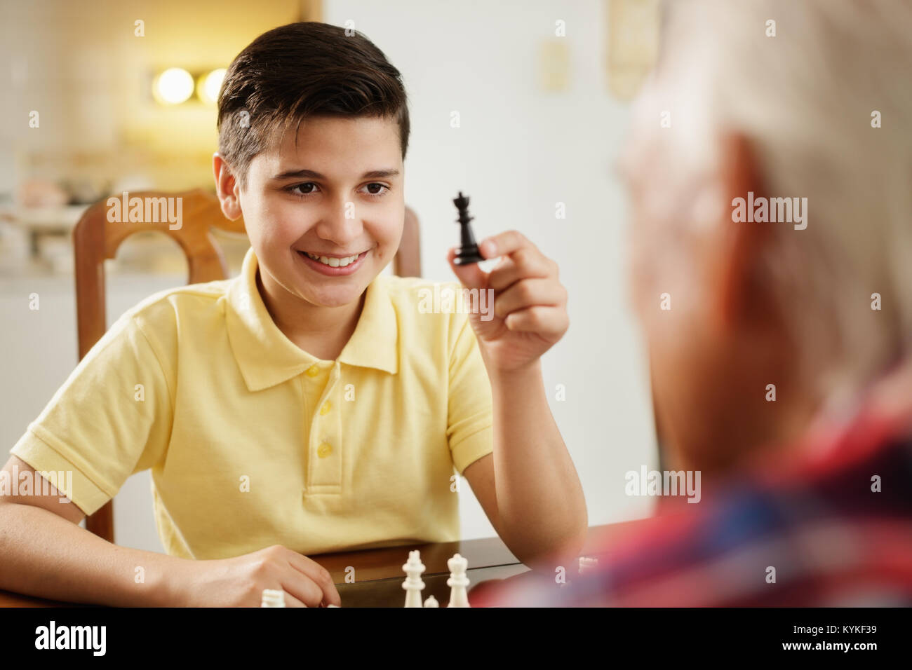 Grandpa Playing Chess Board Game With Grandson At Home - Stock Image