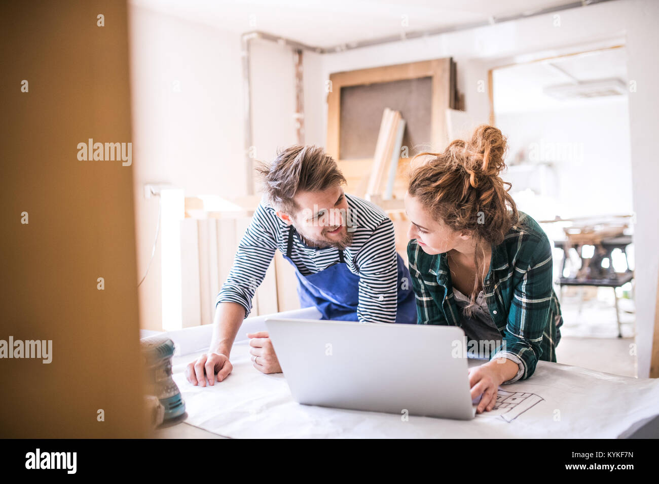 Young couple with laptop in the carpenter workroom. - Stock Image