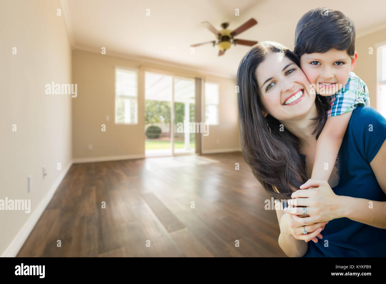 Young Mother and Son Inside Empty Room with Wood Floors. - Stock Image