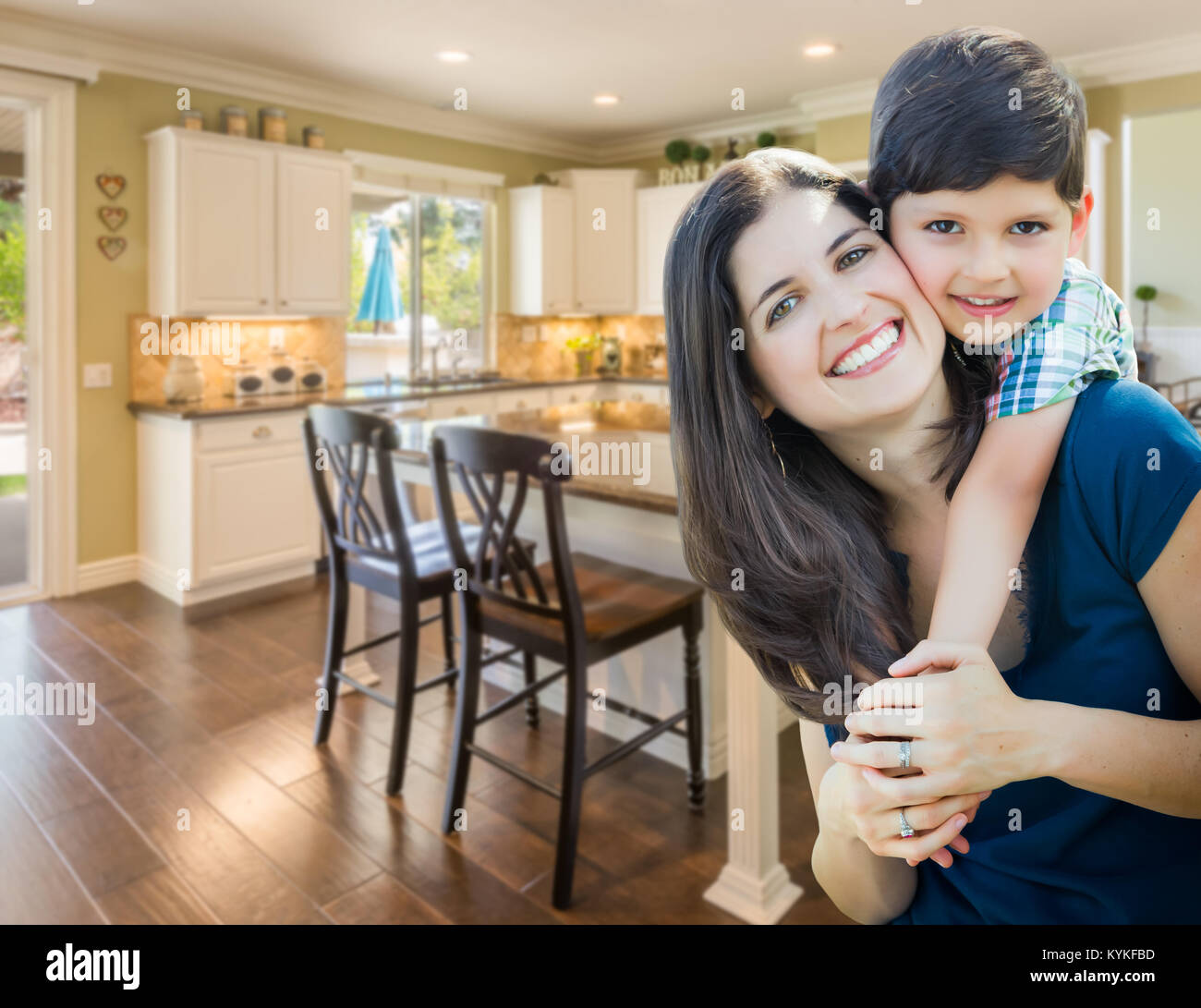 Young Mother and Son Inside Beautiful Custom Kitchen. - Stock Image
