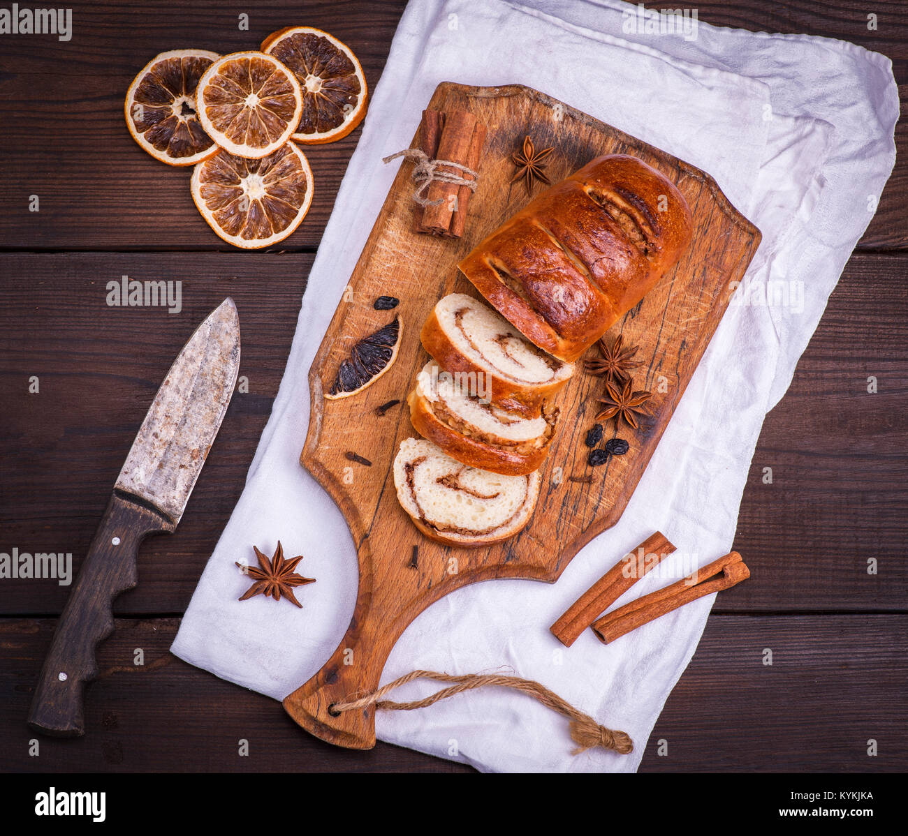 baked roll with cinnamon and nuts on a wooden cutting board, next knife, top view - Stock Image